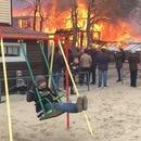 miniature pour Un garçon fait de la balançoire à côté d'une maison qui brûle